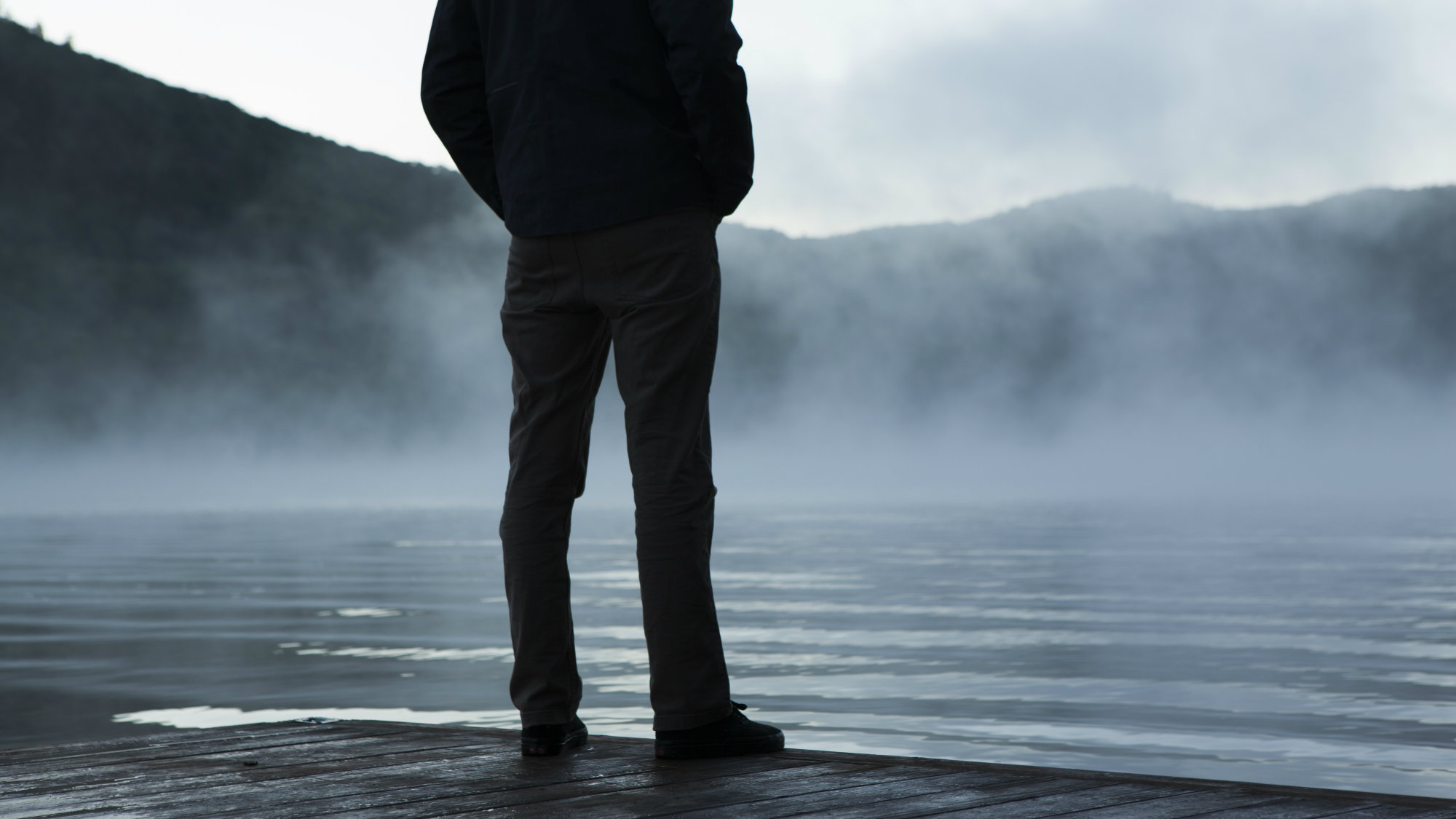 A man overlooks a lake where mist is rising