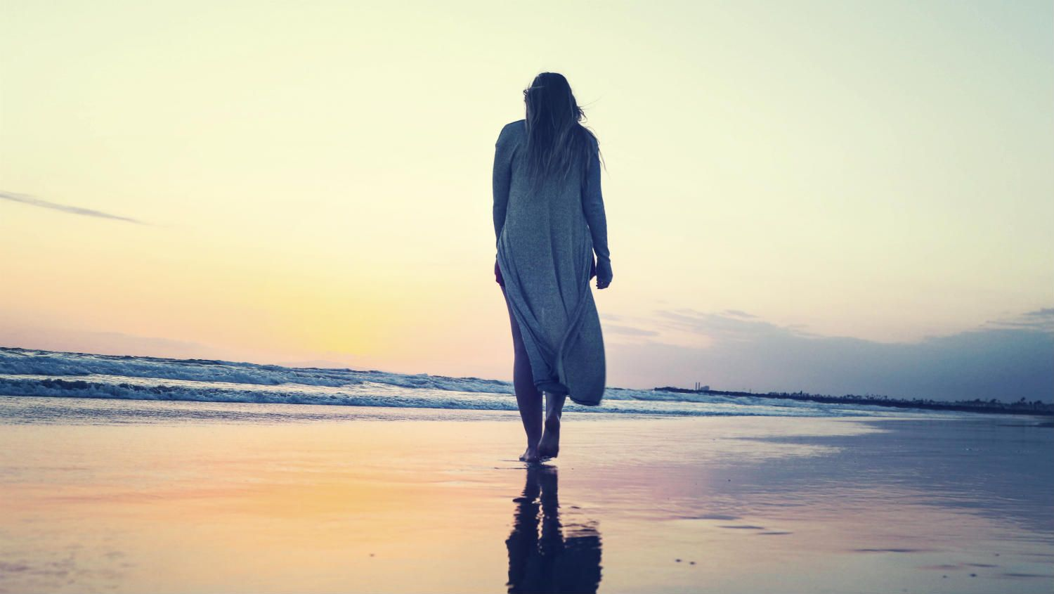 Woman walking alone on a beach